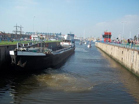 vrachtboot en jachtboten in sluis