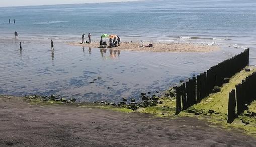 Zoutelande strand opruimen want vloed komt